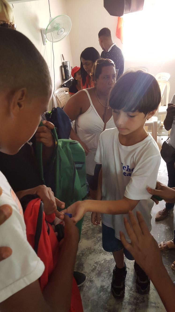 children giving backpack